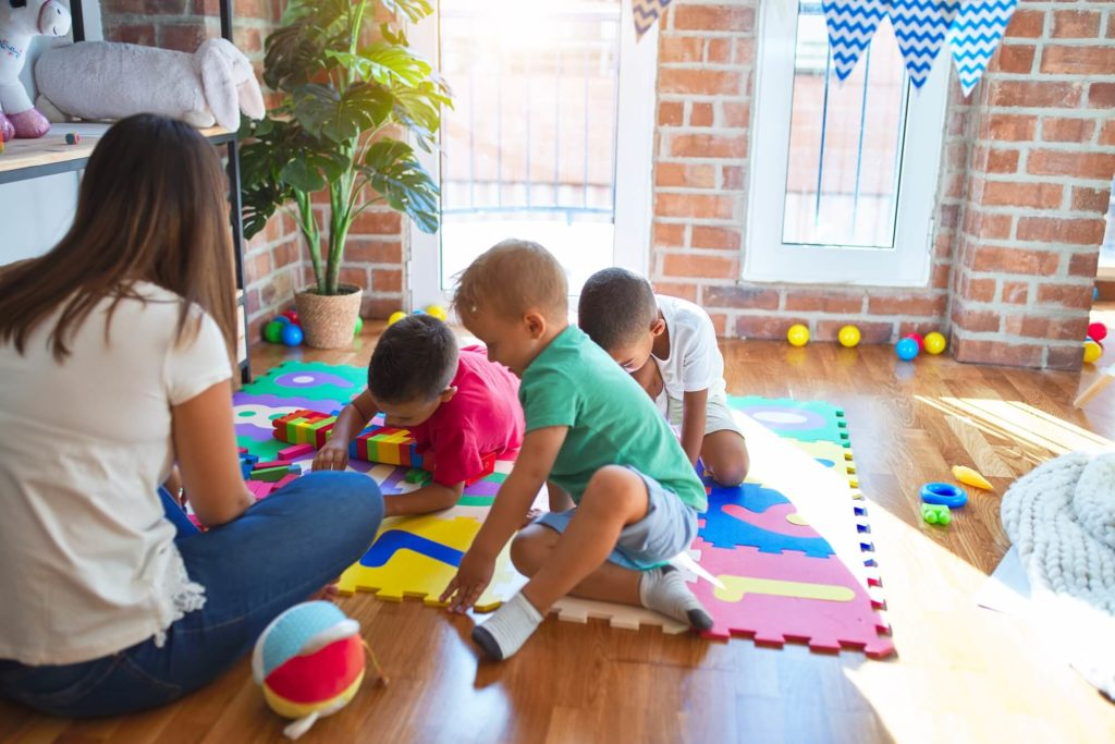 Global Aware Care Childcare Preschool Daycare Educator interacting with Toddler and Preschool children