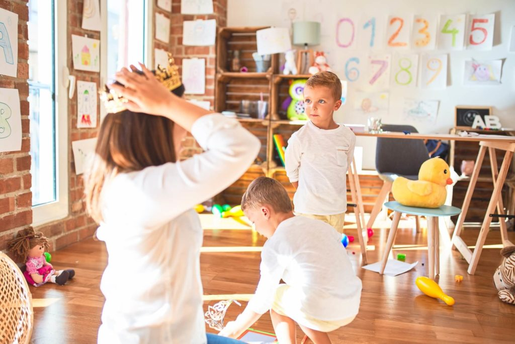Global Aware Care Childcare Daycare Educator playing with Preschool and Toddler children