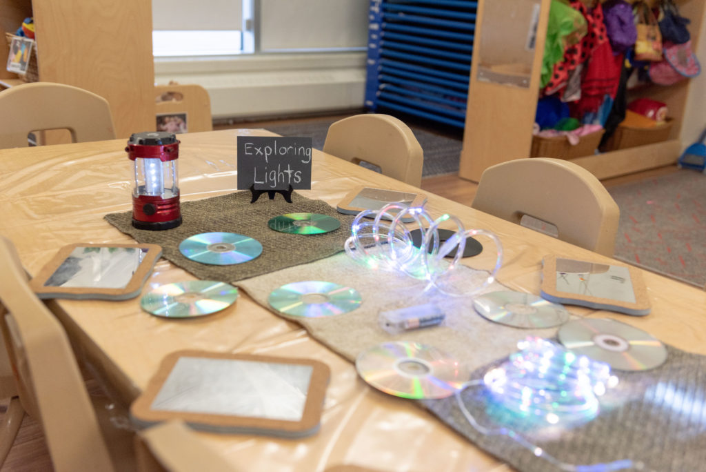 A variety of mirrors and other reflective objects laid out on a table at the Summerside location to encourage toddlers to explore light.